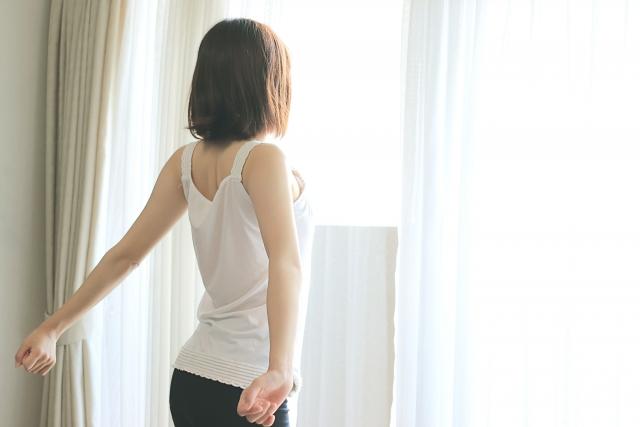 窓に向かって伸びをする女性